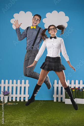 Funny nerdy couple jumping in farm