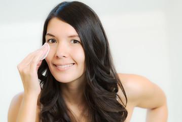 Frau reinigt ihre Haut mit einem Wattepad