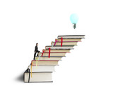 Businessman climbing on stack of books with growing bulb
