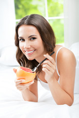 Smiling woman eating grapefruit at home