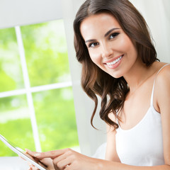 Young woman using tablet pc, at home