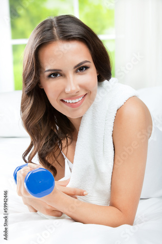 Smiling woman with dumbbell, indoors