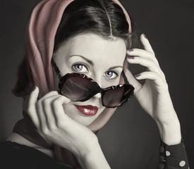 Beautiful woman in big violet fashion sunglasses and shawl.