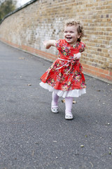 little girl in floral dress swinging arms playfully