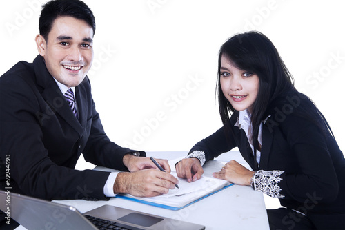 Happy businesspeople signing business contract