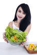 Pretty woman holds vegetable salad