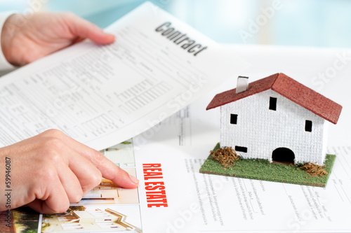 Hands reviewing real estate property documents.