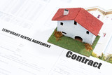 Small wooden house on contract forms.