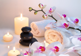 preparation for massage in white with towels, stones, candles