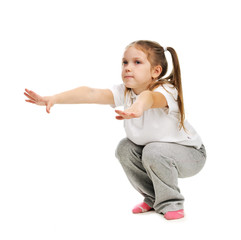 A little girl doing exercises in studio.