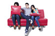 Three young people watching TV