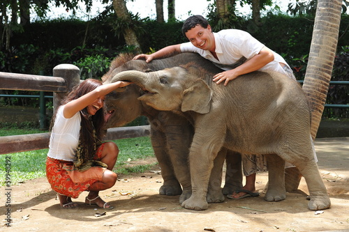 Beautiful couple playing with baby elephants