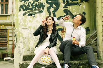 unusual loving wedding couple near wall with graffiti thrown hou