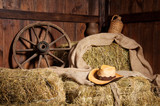 Interior of a rural farm - hay, wheel, cowboy hat.