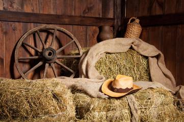 Interior of a rural farm - hay, wheel, cowboy hat.