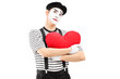 Thoughtful mime artist holding a red heart