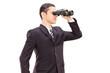 Young businessman looking through binocular