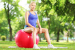 Young female athlete sitting on a fitness ball in park