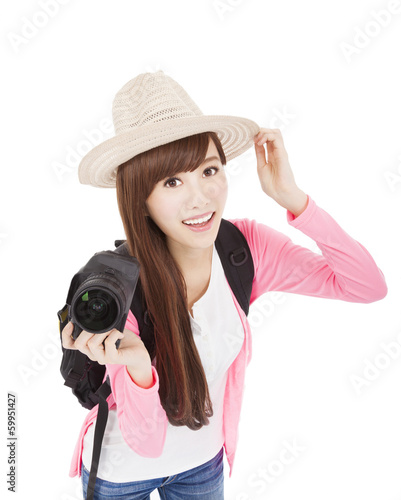 smiling young woman holding a camera and hat