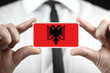 Businessman holding a business card with Albania Flag