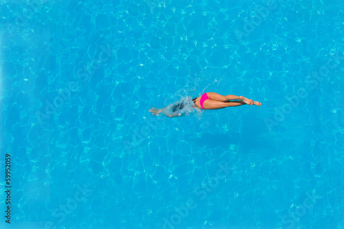 Top view of a girl diving in the pool