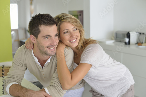 Middle-aged couple standing in home kitchen