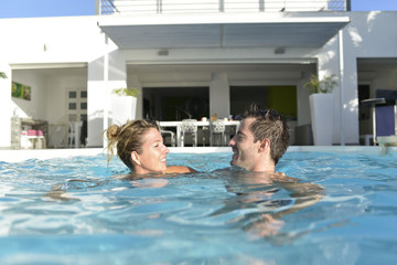 Couple swimming in private luxury pool