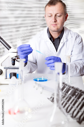 scientist working in the lab , examines a with liquid