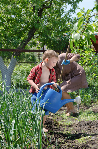 Small boy helping Mum water the vegetable garden