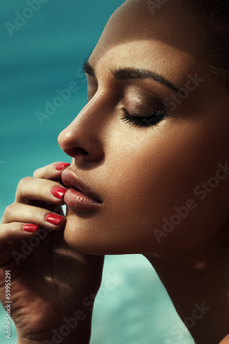 Beautiful young model with bright makeup and manicure