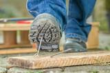Arbeiter mit Sicherheitsschuhen tritt in einen Nagel