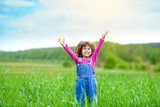 Happy little girl with her hands up on the green wheat field