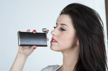 Young woman drinking from a hipflask
