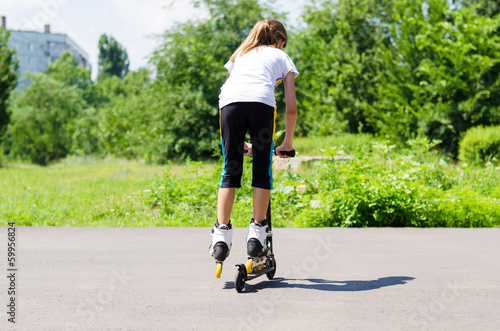 Teenage girl playing on a scooter
