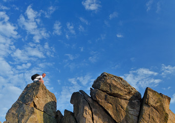 Backpacker on a distant rocky mountain peak