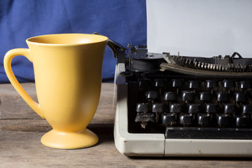 Old typewriter with coffee cup