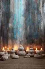Runde Steine und Kerzen vor abstraktem Gemälde