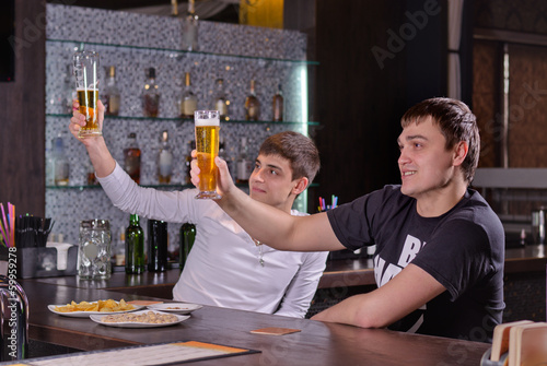 Two young men raising their beers in a toast