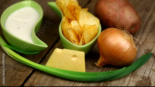 Crispy chips in green bowl on wooden boards