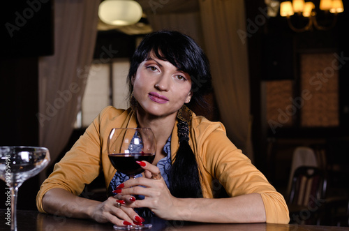 Stylish young woman drinking a glass of red wine