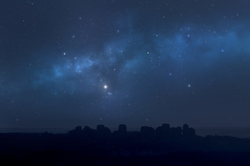City landscape at night with star filled sky, nebula and galaxy