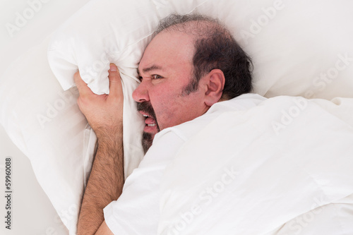Insomniac clutching at his pillow in desperation