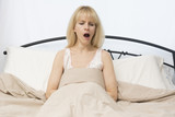 Wake Up Time: Middle Age Woman Yawns In Bed