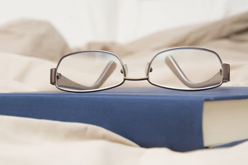 Book and Glassses on Bed