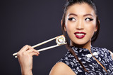 Young beautiful asian woman eating sushi,
