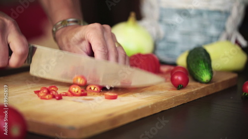 Female hands with knife, cutting fresh red chili peppers, steadi