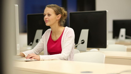 Young female student working alone in a computer classroom