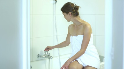 Young woman sitting on a bathtub preparing a bath for herself