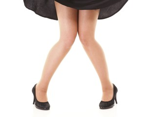Sexy female legs in black skirt and high heels isolated