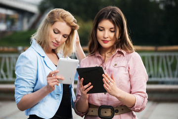 Two young women holding a digital tablet computers